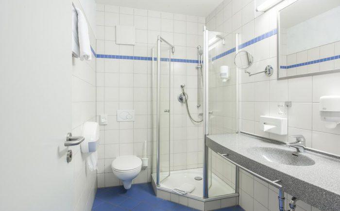 Kurhaushotel Bad Salzhausen kleineres Badezimmer mit allem was man benötigt. Sehr hell beleuchtet und alles was man braucht um sich frisch zu machen.