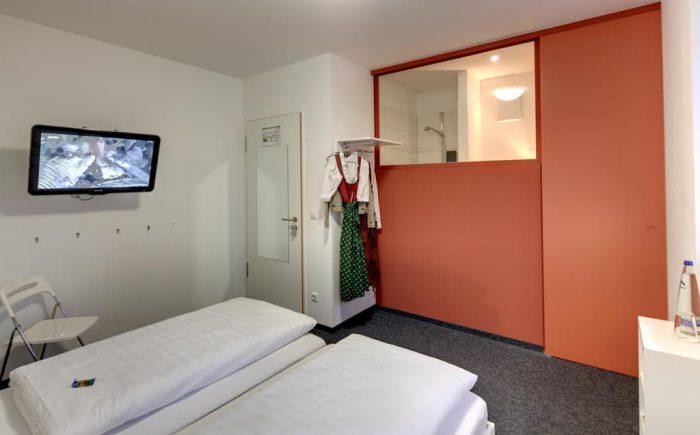 Ein Doppelzimmer mit offenen Dusche und Fernsehr im Zimmer.