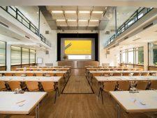 mainhaus-stadthotel-frankfurt ein schöner großer und heller Tagungsraum mit einer großen Bühne.